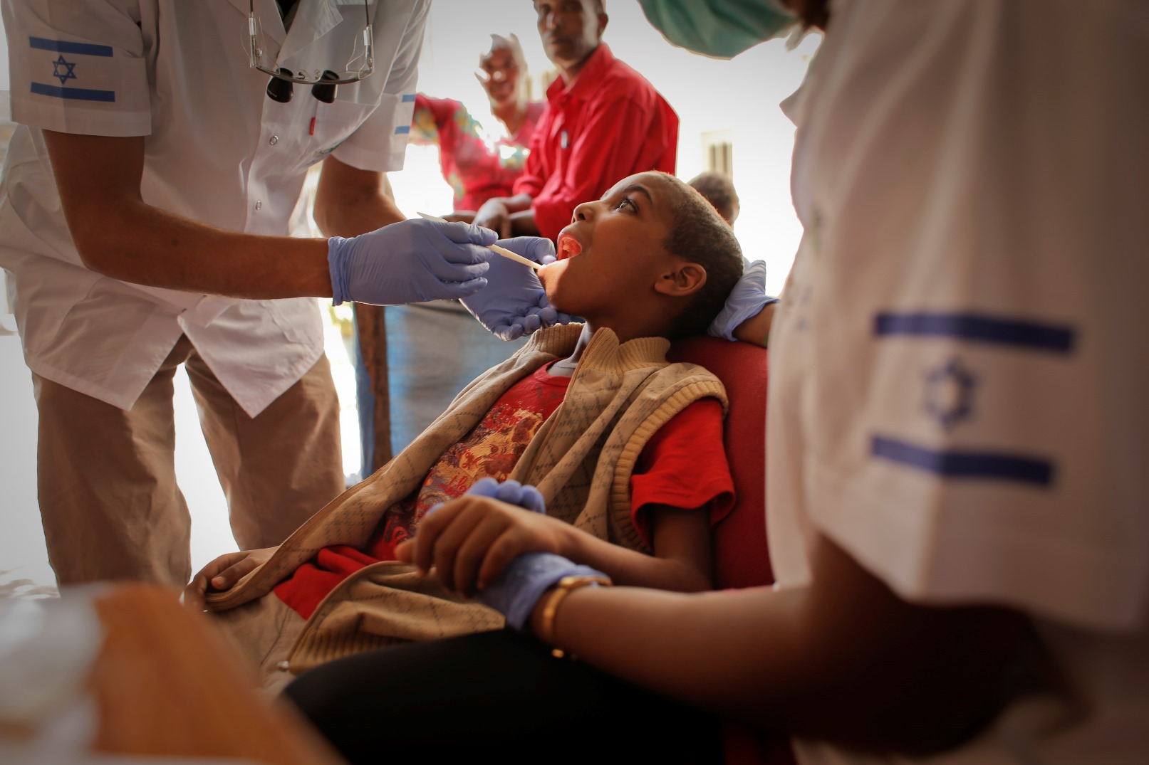 An Israeli dentist and post-army volunteer caring for a child in Ethiopia. Photo courtesy of FFL