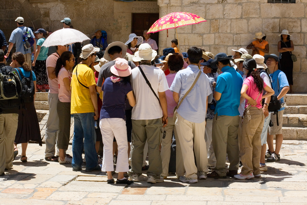A group of Asian tourists listening to a guide at the entrance of the Church of The Holy Sepulcher, Jerusalem. Photo via Shutterstock.com