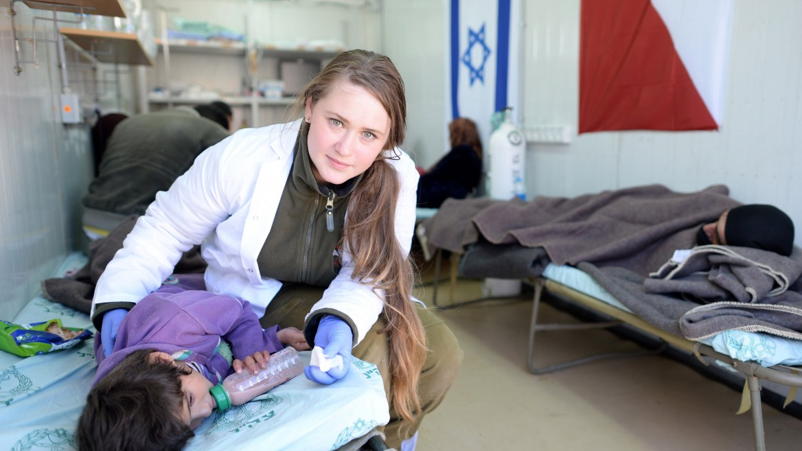 An IDF medic treats an injured Syrian girl at a field hospital in northern Israel. Photo by GPO