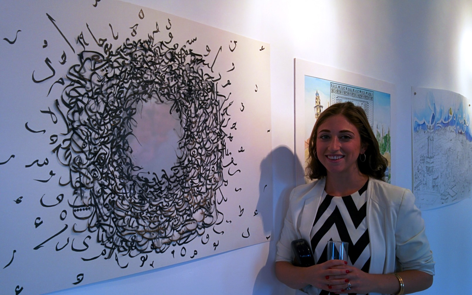 Lenore Cohen with a work in which she placed a muted photo of herself and her father in the center. Photo by Abigail Klein Leichman