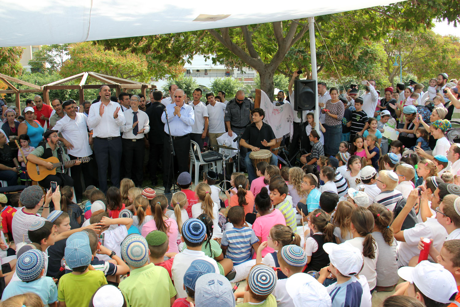 President Reuven Rivlin hosts children for entertainment in his mobile sukkah in Lod during the Sukkot holiday in 2014. Photo by Itzik Edri/GPO