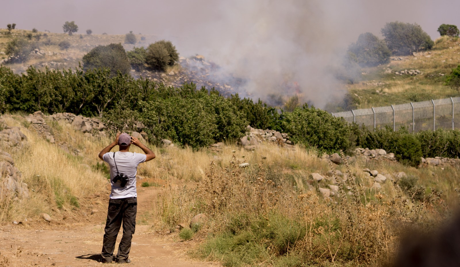 A resident of the Golan Heights in Israel watching the Syrian fighting over the border. Photo by Basel Awidat/FLASH90