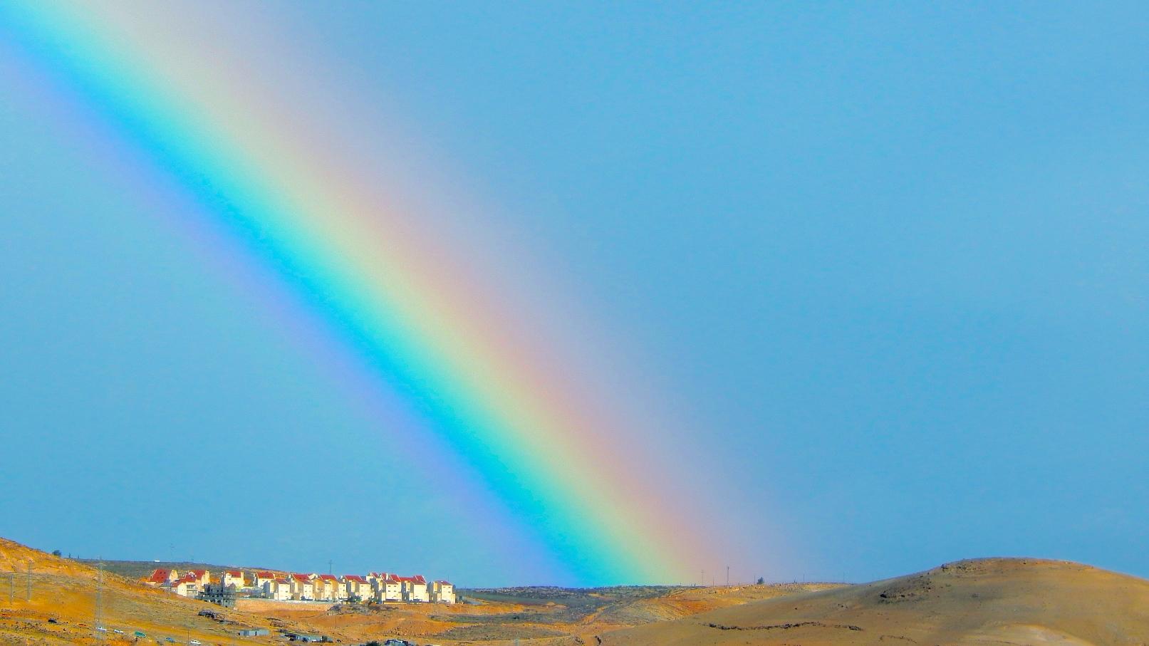 A rainbow arches over Kfar Adumim in the Judean Desert. Photo by Daniel Santacruz