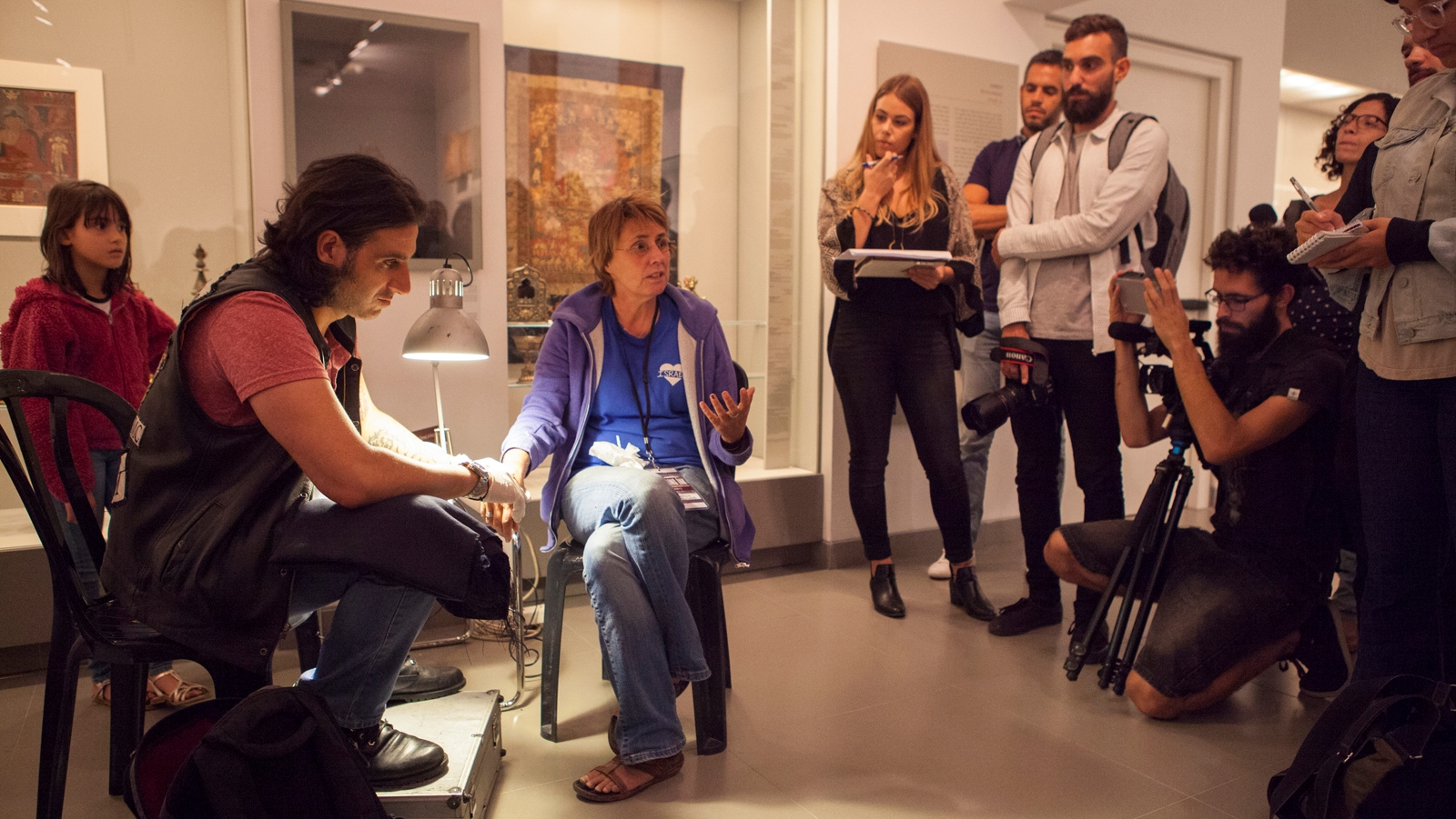 Wassim Razzouk tattoos terror victim Kay Wilson in the Asian Art Wing at the Israel Museum. Photo: courtesy