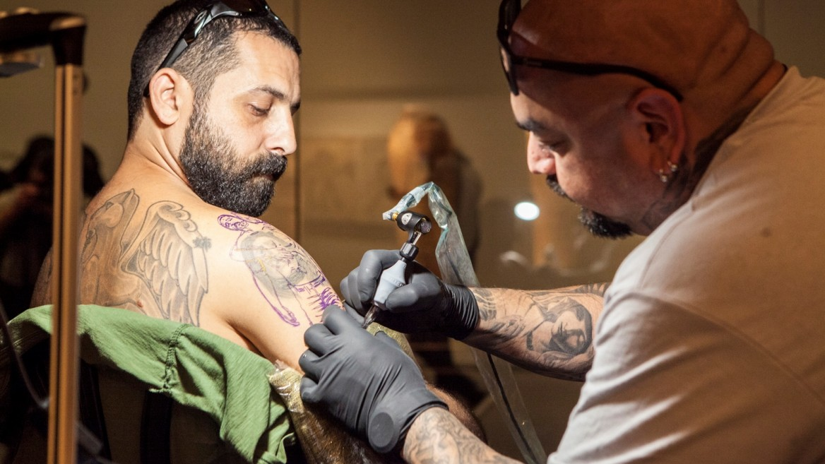 Steve Soto tattoos Barak Miron in the Archeology Wing of the Israel Museum. Photo: courtesy