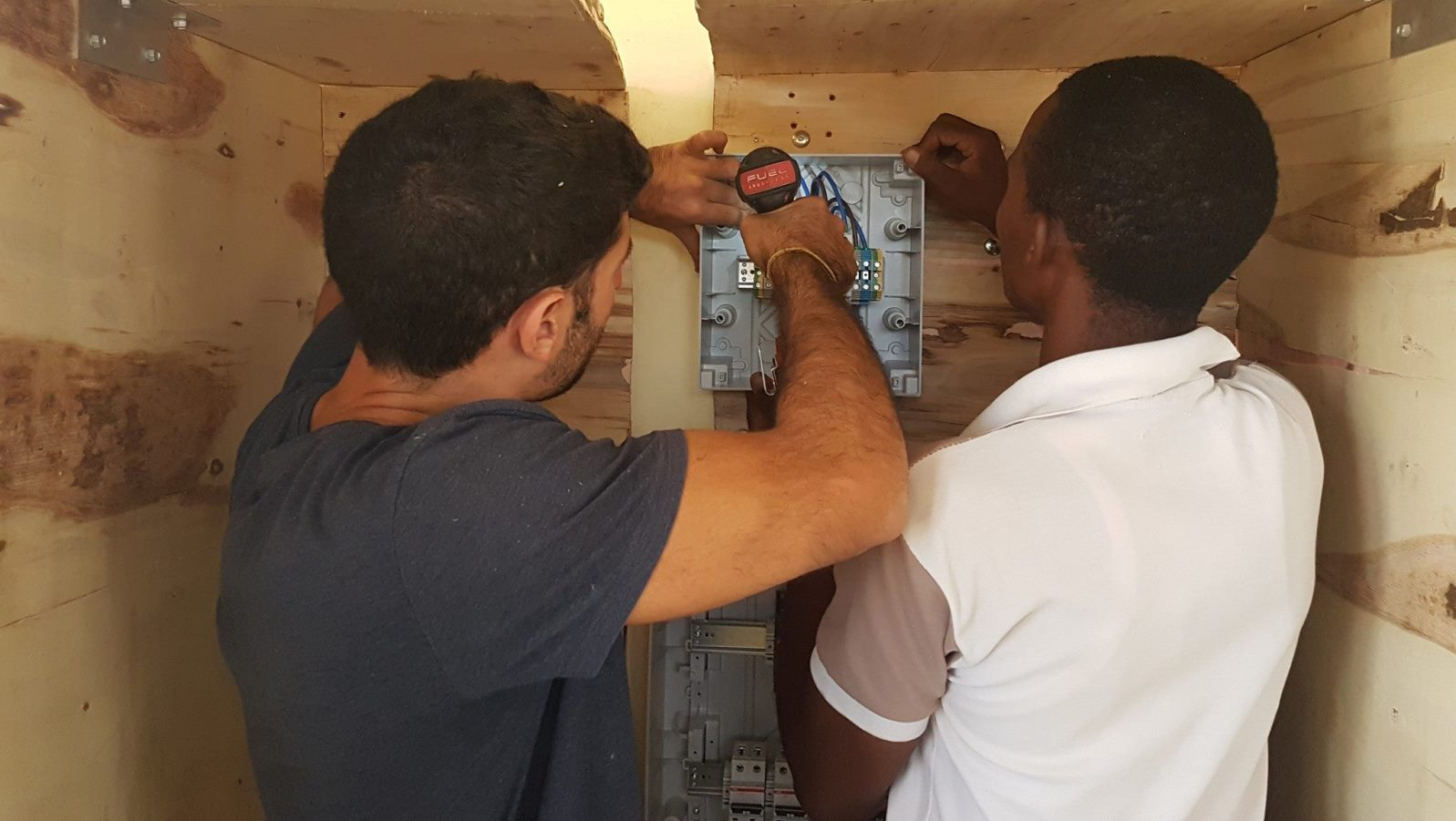 EwB TAU member Raz Cohen working with a Minjingu resident to install the solar generator. Photo via Facebook