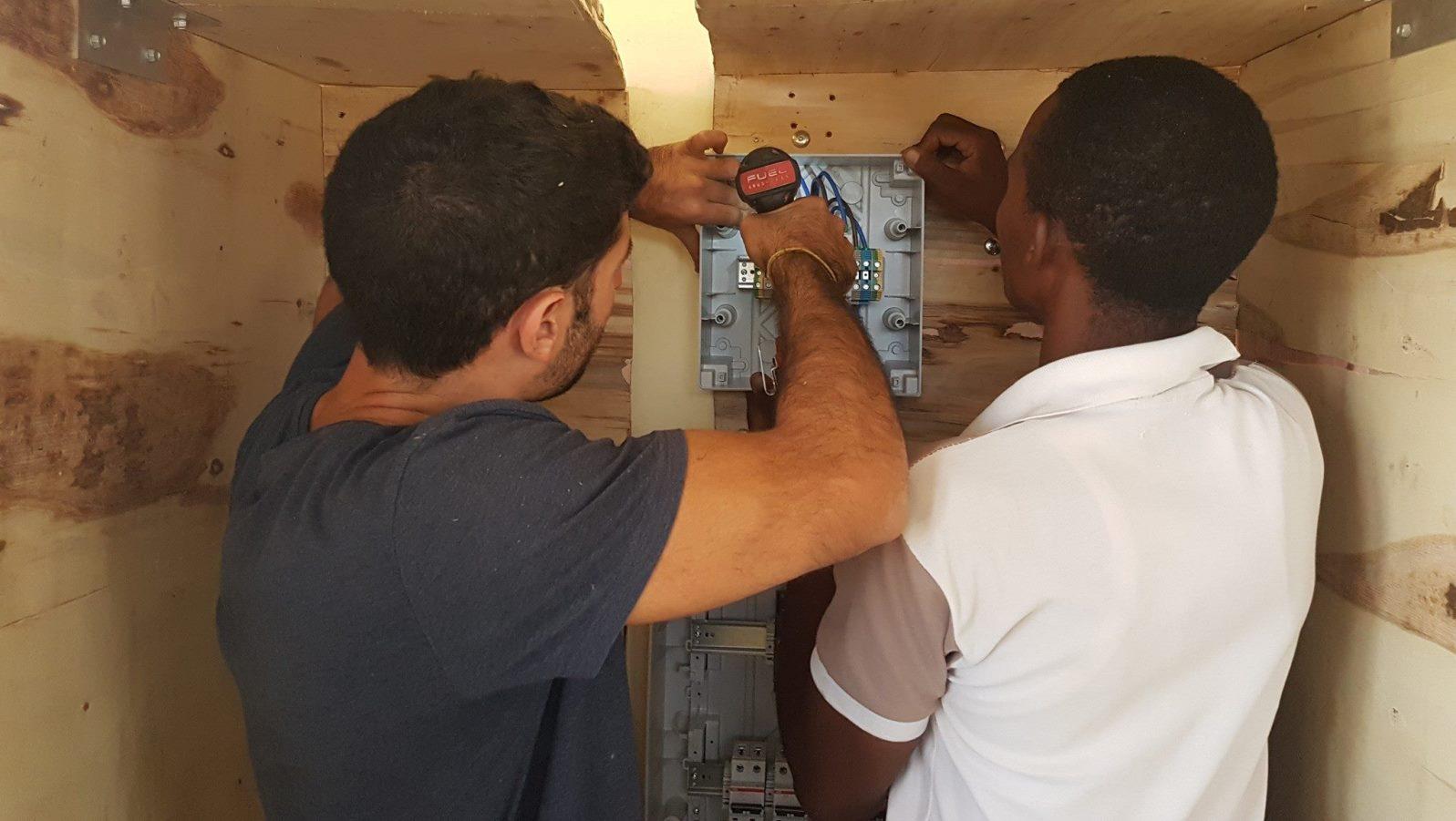 EwB TAU member Raz Cohen working with a Minjingu resident to install the solar generator. Photo via Facebook