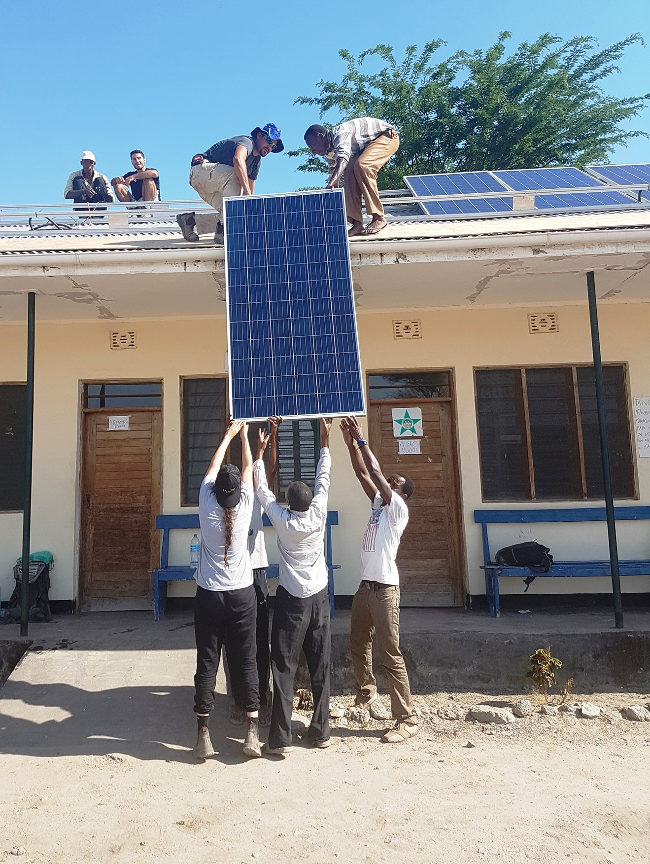 EwB TAU and local volunteers installing solar panels on the clinic's roof. Photo via Facebook