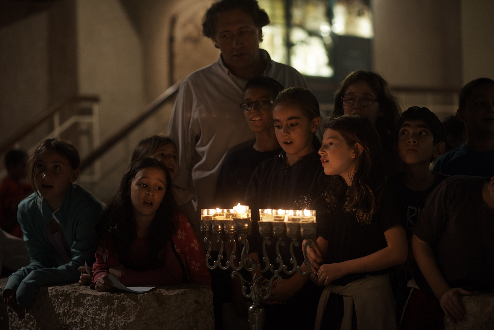 Children singing after lighting a hanukkiah in the Old City of Jerusalem. Photo by Yael Harman
