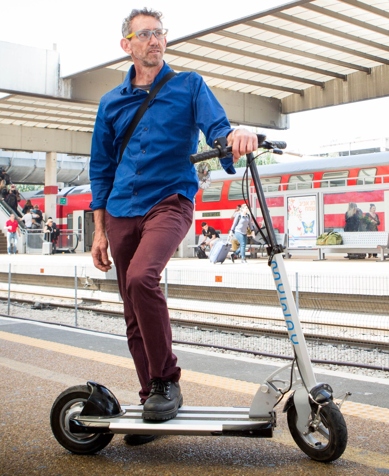 Inokim designer Nimrod Sapir with one of his scooters at an Israeli railroad station. Photo by Shlomi Yosef