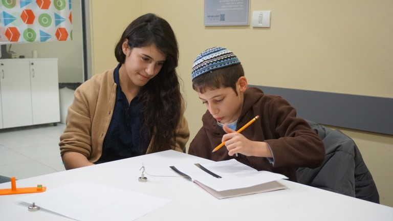 Ido trying out the adapted ruler for the first time with Hila Moore. Photo courtesy of TOM:Tikkun Olam Makers