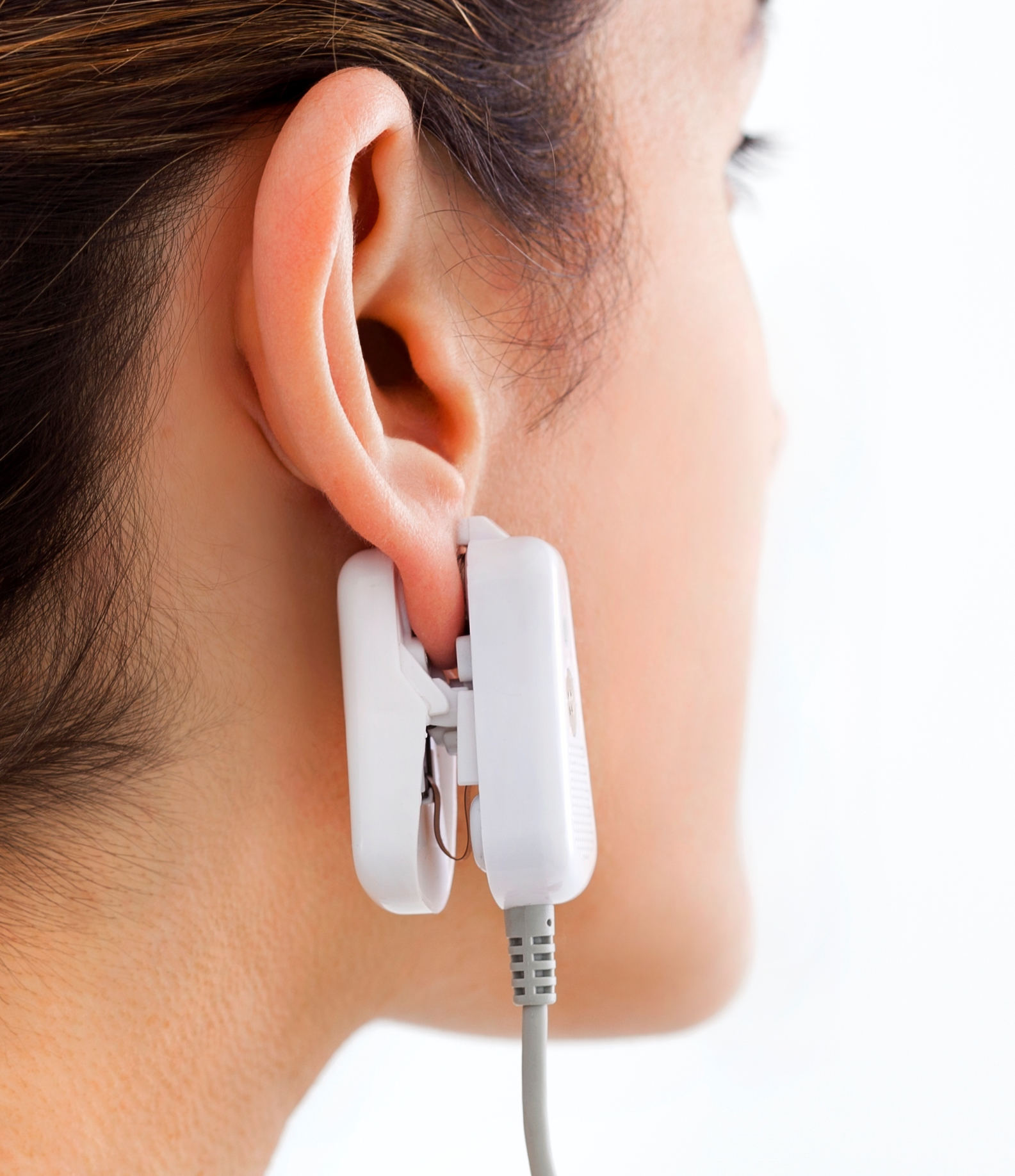 GlucoTrack users test glucose levels with an ear clip attached to a handheld control unit. Photo: courtesy