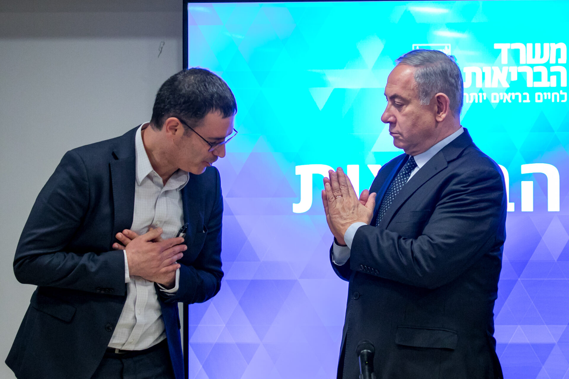 Israeli Prime Minister Benjamin Netanyahu, right, and Director General of the Ministry of Health Moshe Bar Siman Tov demonstrate how to greet one another without shaking hands due to coronavirus concerns, March 4, 2020. Photo by Olivier Fitoussi/Flash90