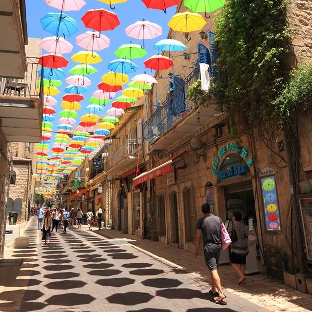 Colorful umbrellas floating in the sunny blue sky above Yoel Moshe Salomon Street where galleries, ceramics, arts jewelry and clothing shops line the Jerusalem street.