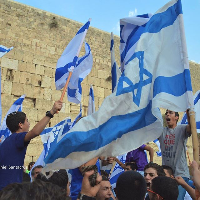 Students wave #Israeli flags in front of the #Kotel in Jerusalem\'s Old City. #IsraeliPride  Photo credit: Daniel Santacruz
